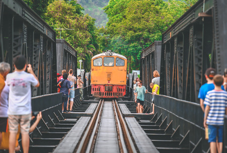 KANCHANABURI, THAILAND - JULY 9, 2016: Tourists taking pictures the train on the bridge over the river Kwai in Kanchanaburi, Thailand. This bridge is famous for its history in second world war