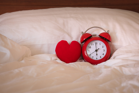 Red alarm Clock and heart shape on white bed sheet against the pillow, sleep well concept Stock Photo