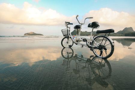 ビーチで、ビーチでの反射とのタンデム自転車、穀物テクスチャ スタイルを適用します。