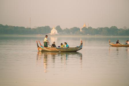 Mandalay, Myanmar - 3 February 2017: Tourists watching the sunset on tradition boast at  Taungthaman Lake Amarapura. U Bein Bridge, Mandalay