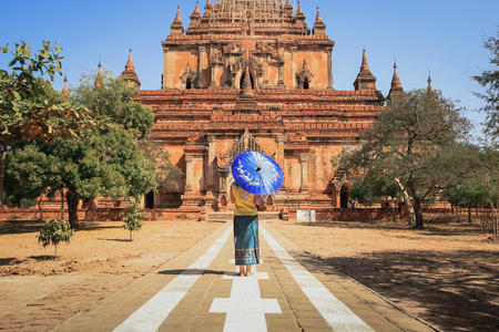 Back side of burmese woman holding traditional blue umbrella walking at temple in Bagan, Myanmar