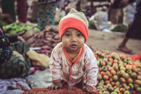 BAGAN, MYANMAR - Fabruary 3, 2017 : Lively young Burmese kid ready to contribute to fresh food sales in the morning market Editorial