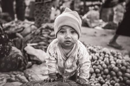 BAGAN, MYANMAR - Fabruary 3, 2017 : Lively young Burmese kid ready to contribute to fresh food sales in the morning market, black and white Editorial