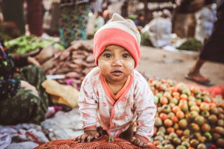 BAGAN, MYANMAR - Fabruary 3, 2017 : Lively young Burmese kid ready to contribute to fresh food sales in the morning market Stock Photo - 72823711