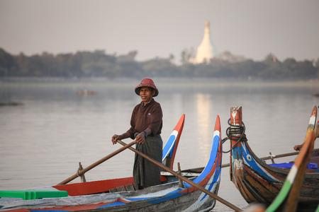 boatman: Mandalay, Myanmar - 3 February 2017:Burmese boatman waiting for tourists watching the sunset on tradition boast at  Taungthaman Lake Amarapura. U Bein Bridge, Mandalay