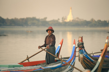 Mandalay, Myanmar - 3 February 2017:Burmese boatman waiting for tourists watching the sunset on tradition boast at  Taungthaman Lake Amarapura. U Bein Bridge, Mandalay