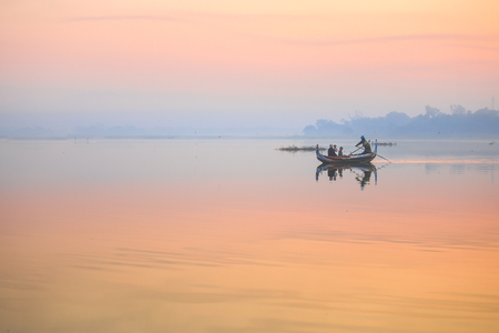 Foggy landscape with tourists on the boat taking picture of the sunset on tradition boast at  Taungthaman Lake Amarapura. U Bein Bridge, Mandalay