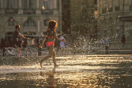 hottest: BORDEAUX, FRANCE - 3 April, 2017 : Little girl enjoy walking at Bordeaux water mirror in the hottest day during the sunset with water splash, grain texture style apply