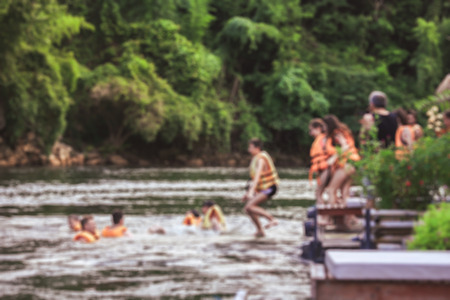 Blurred of group of friends jumping on the river kwai, Kanchanaburi during the vacation. Concept about vacations, leisure and fun