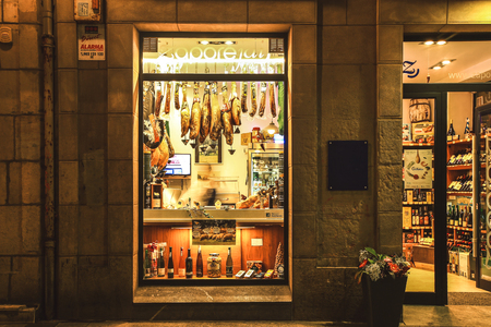 SPAIN SAN-SEBASTIAN - OCTOBER 27, 2017 : Jamon, facade of the souvenir store selling traditional spanish pork legs, hanging in the shop, night street view