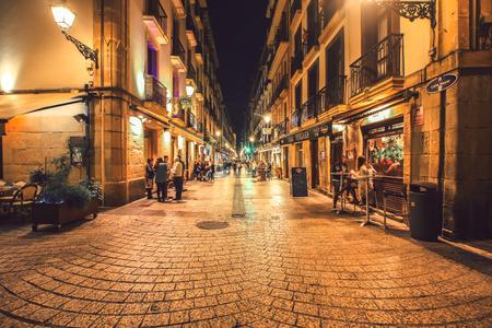 SPAIN SAN-SEBASTIAN - OCTOBER 27.2017 : San Sebastian typical small street view with lively tapas bars and restaurants at night