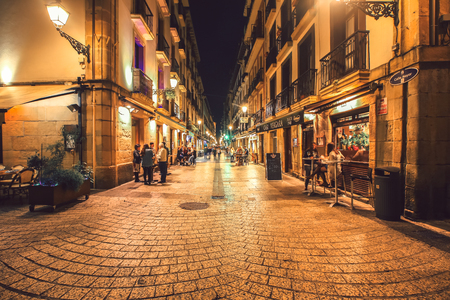 SPAIN SAN-SEBASTIAN - OCTOBER 27.2017 : San Sebastian typical small street view with lively tapas bars and restaurants at night