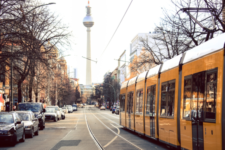 Yellow public transportation tram passing by the city of Berlin Germany