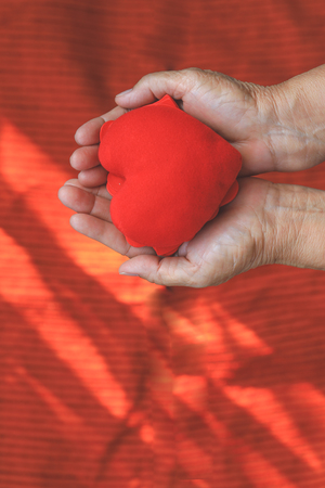 Selective focus on red heart shape on hands top view. Healthy, donation, organ donor, hope and cardiology concept. Stock Photo