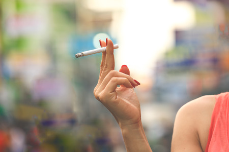 Female hand holding cigarette with nails painted on colourful background Stock Photo