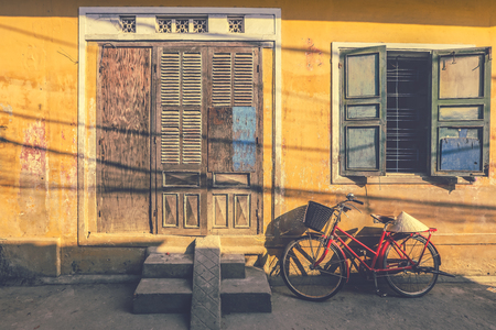 Bicycles parked near yellow wall of old house in Hoi An, Vietnam