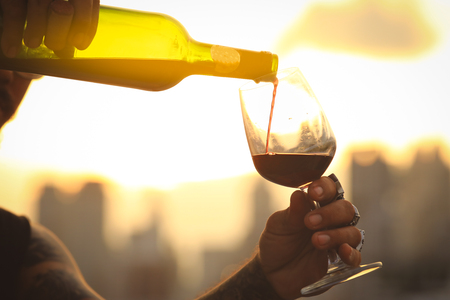 Glass and bottle of red wine in selective focus on glass of wine. pouring red wine at sunset