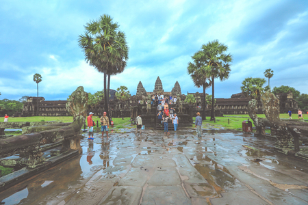 Siem Reap, Cambodia - March 22, 2018 : Tourists visiting Angkor Wat temple under the rain in Siem Reap. Angkor Wat is the largest religious monument in the world.