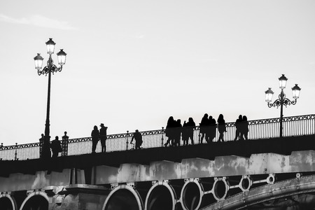Silhouettes of people crossing the bridge. black and white photography