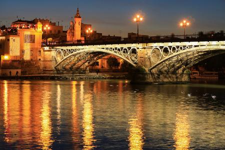 Isabel II bridge or Triana bridge over Guadalquivir river at twilight, Seville, Andalusia, Spain