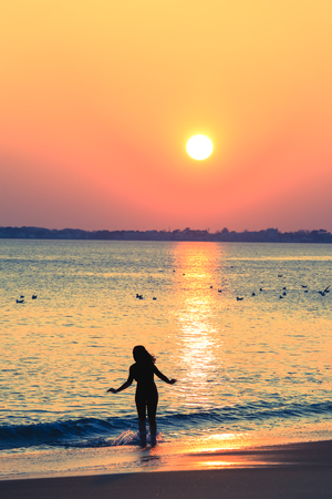 Silhouette of slim woman on the beach  during amazing sunset.