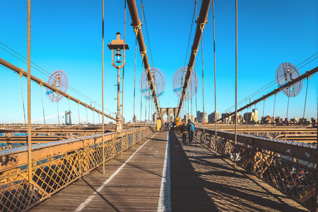 Full of tourists walking on Brooklyn Bridge in a beautiful day, New York