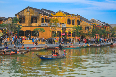 Hoi An, Vietnam - February 9, 2018 : Selective focus on tourists sit on small wooden boat with Vietnamese people rowing. See around the ancient town Editorial