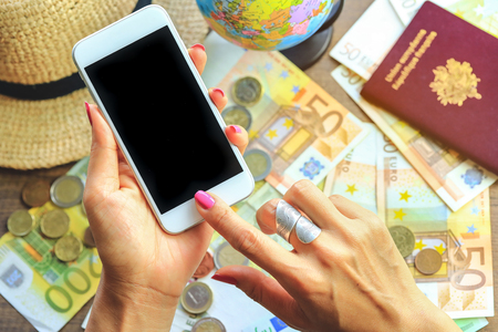 Hands holding smart phone with Euro money banknotes bills as travel passport on copy space background. Travelling light, comfortable journey concept.