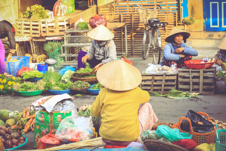 Hoi An, Vietnam - February 7, 2018 : Soft focus on Vietnamese woman selling vegetables on a roadside market in Hoi An, Quang Nam Province, Vietnam.