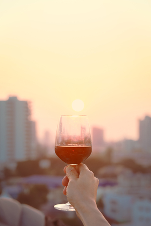 Close up on man's hands holding red wine glasses on balcony during sunset, celebration concept Imagens