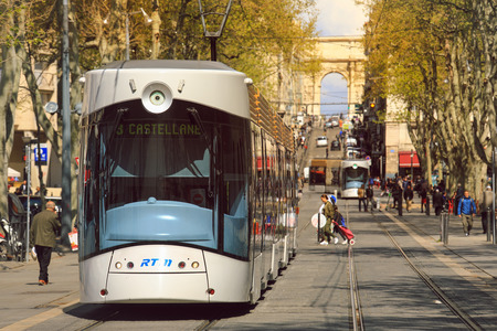Marseille, France - April 7 2019 : Modern tramway passing by the center in Marseille with Porte Royale - triumphal arch on the back