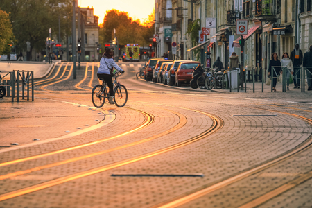 BORDEAUX, FRANCE- October 1, 2018 : Selective focus on pavement, city street scene, people walking on street with tramway during the sunset in Bordeaux, France