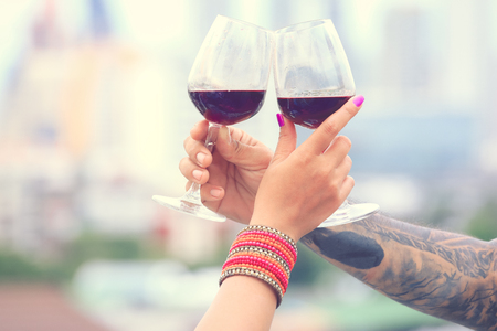 Close up on hands holding red wine glasses on balcony in vintage style, celebration concept