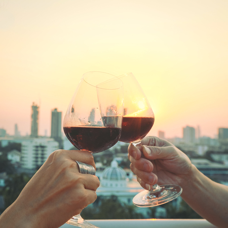 Close up on hands holding red wine glasses on balcony during sunset, celebration concept Imagens