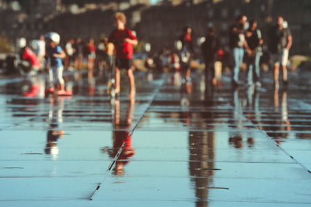 Abstract blurred image of people on water mirror in Bordeaux, France