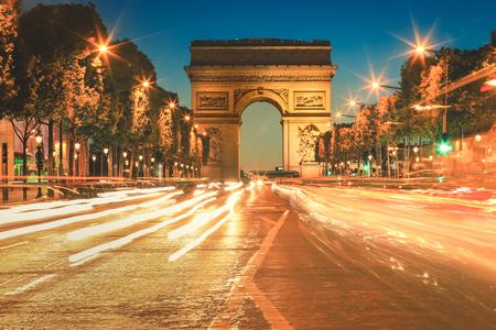 Avenue des Champs Elysees. Arc De Triomphe and light trails at twilight, Paris