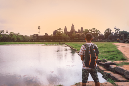 Tourist looking at Angkor Wat temple in Siem Reap,  Cambodia. Angkor Wat is the largest religious monument in the world.