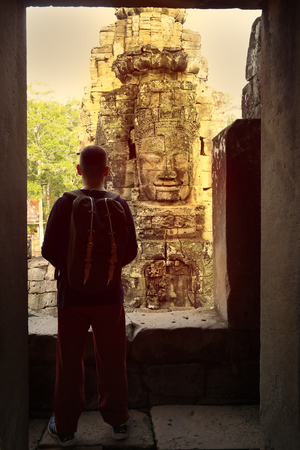 Tourisrt looking at stone face at the Bayon Temple in the Temple City of Angkor near the City of Siem Reap , Cambodia Imagens