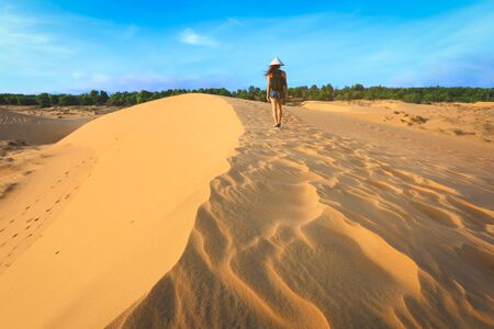 back side of woman walking on red sand dune in Mui ne, Vietnam Imagens