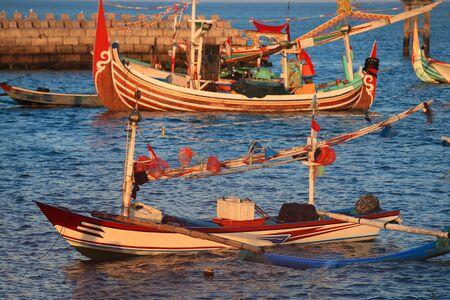 Colorful handcrafted Balinese wooden fishing boat at port in Jimbaran beach, Bali Foto de archivo - 124604525