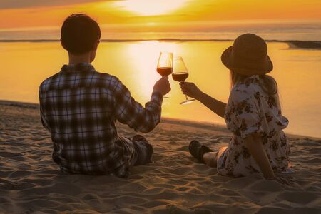 Couple celebration drinking red wine at sunset beach