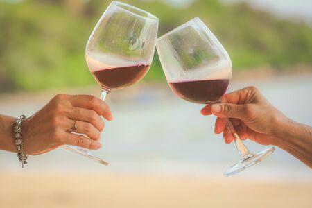 Cerca de las manos sosteniendo copas de vino tinto en la playa, concepto de celebración