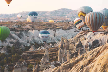 Cappadocia, Turkey - October 19, 2019 : Colorful hot air balloons flying over the valley at Cappadocia. Hot air balloons are traditional touristic attraction in Cappadocia.