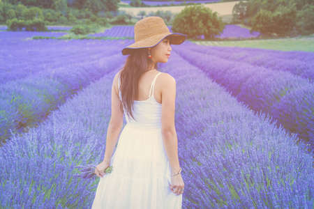 Woman in white dress and hat back view walking  on the lavender field Stock Photo