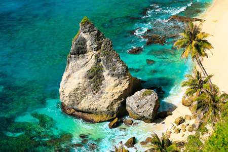 Beautiful beach. selective focus on big rock on nice tropical beach with palms trees. Holiday and vacation concept. Stock fotó