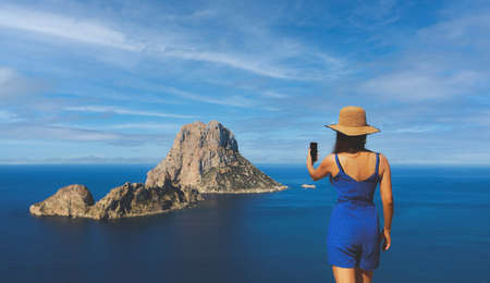 Asian woman selfie in front of the islet of Es Vedra in Spain by the sea in summer in Cala dhort