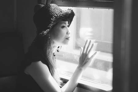 Smiling asian woman looking through old retro train window, traveling concept