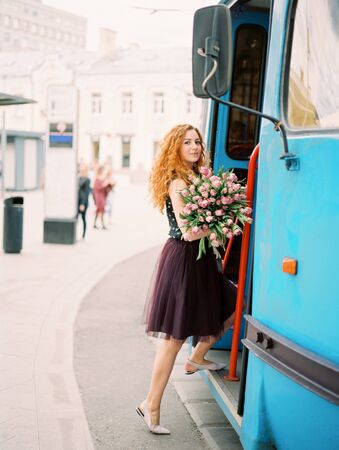 Young beauty woman with flower bouquet on the spring street. film analog photography