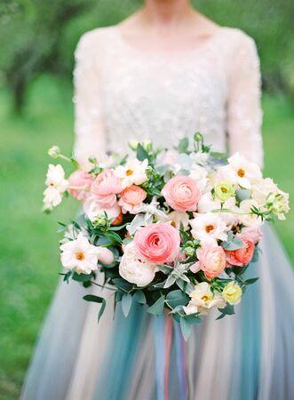 schöne Braut im weißen Hochzeitskleid mit einem Blumenstrauß. analoge Filmfotografie