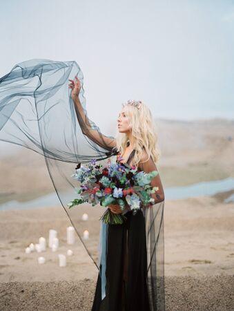 Halloween sexy witch woman portrait, dark dress and bouquet, gold diadem, gothic details, wedding bride style Imagens